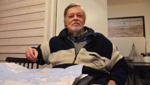 En äldre man i randig tröja sitter tillbakalutad på en stol. På bordet framför honom ligger en karta.