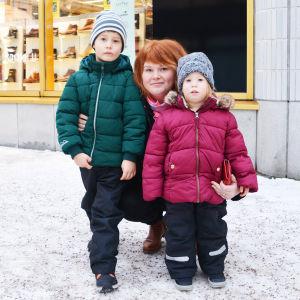 En kvinna sitter på knä och håller armarna om två barn, en flicka och en pojke. Familjen är utomhus i en snöig stadsmiljö.