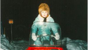 Bild från 80-talet av Tanja Poutianen som i stor pälsmössa kör en röd snöskoter.