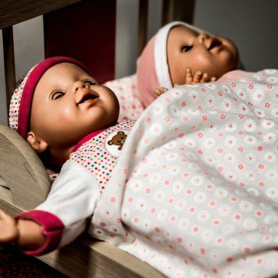 Kaksi nukkea nukkesängyssä.