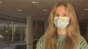 Linnéa Ahti, en ung dam med munskydd, långt ljust hår och grön tröja, står i en korridor.