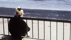 Kvinna vänder ryggen mot kameran, lutar sig mot ett staket