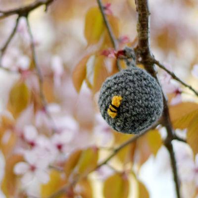 En virkad boll som ser ut som ett getingbo är upphängt i ett träd som blommar.