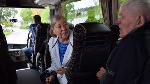 Anna-Lisa Rosenqvist talar med en äldre person ombord på bussen.