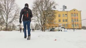 Axel går till gymnasiet. Det är snö på marken. Han har sin ryggsäck på ryggen.