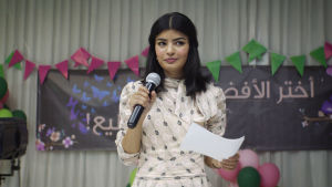 Närbild på Maryam (Mila Al Zahrani) då hon står på scen och håller ett tal.