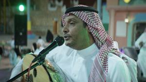 Närbild på Abdulaziz (Khalid Abdulrahim) på scen då han spelar på en oud.