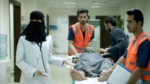 Maryam (Mila Al Zahrani) i sjukhuset, går bredvid en man som ligger på en bår.