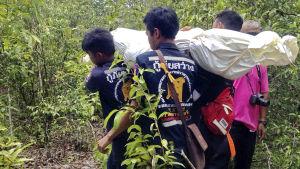 Thailändska räddningsarbetare bär på en död kropp inlindad i vitt plast.