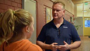 Anders Strömsund talar med några elever i en skolkorridor.