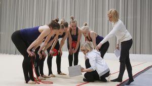 Finlands trupp i rytmisk gymnastik tittar på sitt uppträdande på en ipad.