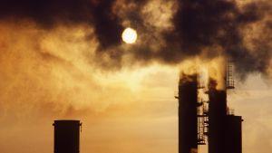 Solen syns genom ett tjockt moln av avgaser från en industripipa