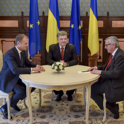 European Council President Donald Tusk, Ukrainian President Petro Poroshenko (C) and European Commission President Jean-Claude Juncker (R) speak during their meeting near the Presidential office in Kiev, Ukraine,