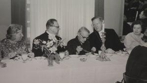 Svartvit, gammal bild där två präster diskuterar över huvudet på en äldre dam
