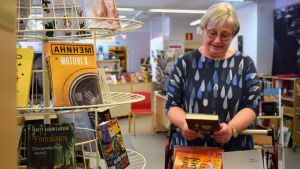 Bibliotekschef Eija Sjöblom ser ner i en bok intill en bokställning.