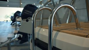 Badstegen till en motorbåt inne i en båtbutik. Båtmotorer i bakgrunden.