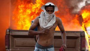 Ung man springer undan sammandrabbningarna i staden Pacaraima vid gränsen mellan Venezuela och Brasilien