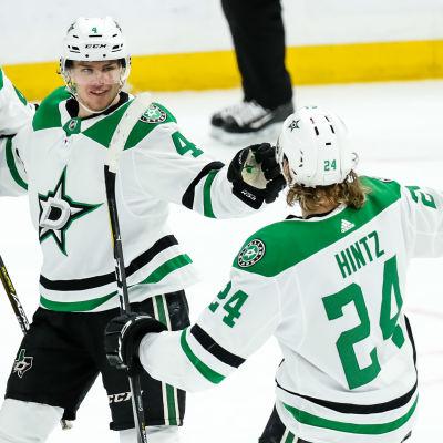 Roope Hintz och Miro Heiskanen reagerar på isen iklädda lagets vita och gröna tröjor och full ishockeymundering.