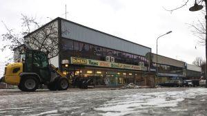 Slitna affärsbyggnader från 1960- eller 1970-talet. En liten snötraktor kör på gatan. En grå vinterdag, lite is och snö på gatan.