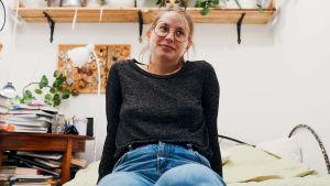 Nainen istuu sängyn laidalla