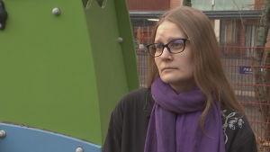 En kvinna i glasögon i en lekpark.