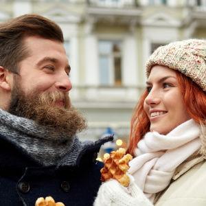 En man med skägg och en kvinna tittar på varandra. Båda ler och har varsin våffla i handen.