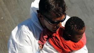 En spansk räddningsarbetare håller i en baby som räddades utanför Libyens kust den 19 juli.