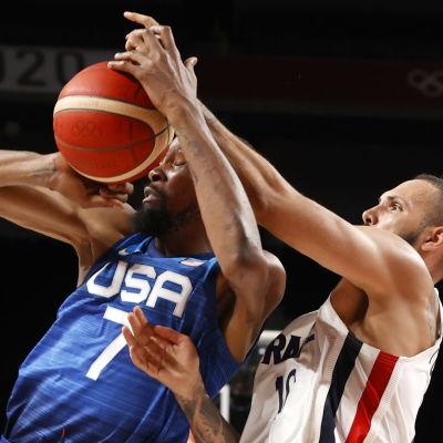 Kevin Durant i blå tröja får bollen i ansiktet i en duell med Evan Fournier i vit blus.