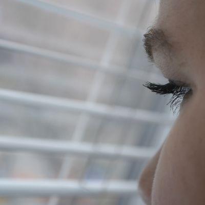 Nainen katsoo sälekaihdinten välistä ulos.