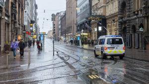Polisbil kör bland människor på Alexandersgatan i Helsingfors.