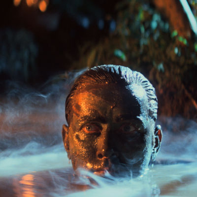 Benjamin Willards (Martin Sheen) huvud dyker upp ur vattenytan, ansiktet är svartmålat och det vattnet ryker av ånga.