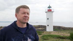 Porträttbild på Pekka Väisänen med Gustavsvärns fyr i bakgrunden.