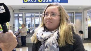 Blond kvinna med blå och vit halsduk blir intervjuad för tv-nytt.
