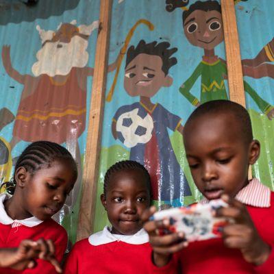 Kolme lasta pelaa kännykällä Kiberan slummissa Kenian pääkaupunki Nairobissa.