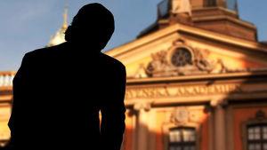 Ryggen av en okänd man som tittar på svenska akedemiens byggnad