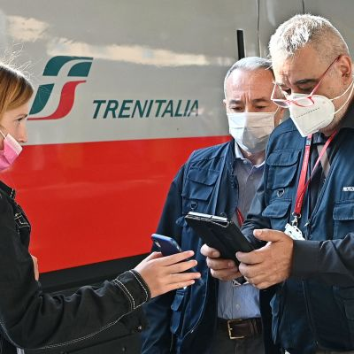 Två män kontrollerar en kvinna coronapass framför ett tåg i Italien