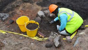 En person i hjälm och gul väst gräver i jorden. Bredvid henne står två gula hinkar.
