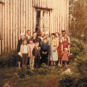 Perhe koossa talon edustalla. Kuva dokumenttielokuvasta Family Files - Perheeni tarina