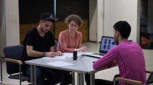 Tre personer vid ett bord, två unga män och en kvinna, sitter och jobbar med något. Ena mannen antecknar på ett papper, de två andra ser på. På borde syns en dator och på skärmen foton.