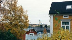 Syksyinen näkymä oululaisessa puutalokorttelissa. Horisontissa näkyy kirkon torni.
