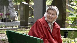En äldre kvinna tittar över nacken på vad som händer bakom henne på den judiska kyrkogården i Vilnius.