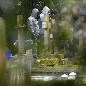Poliser i skyddsdräkter arbetade på begravningsplatsen i Salisbury också på lördagen 10.3.2018.