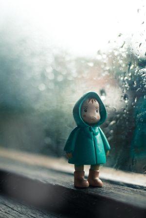 En modellfigur står på ett fönsterbräde med regn på fönstret i bakgrunden.
