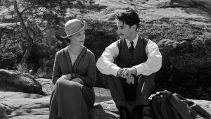 Anna och Adrian sitter på ett berg och tittar på varandra.