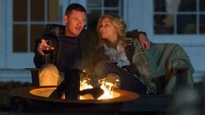 Ett förälskat par sitter vid en brasa med vinglas i händerna.