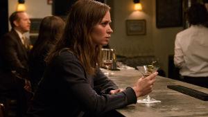 Rachel sitter ensam vid en bardisk med ett halvtomt glas gin framför sig.