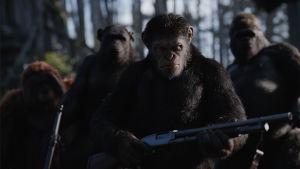 Caesar (Andy Serkis) står med ett vapen i hand och de andra aporna står bakom honom.