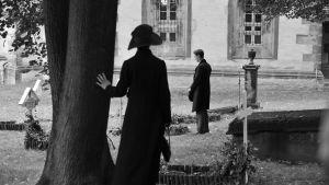 Anna iakttar Adrian där han står vid Frantz grav.