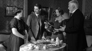 Anna och Frantz föräldrar diksuterar med Adrien runt kaffebordet.