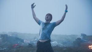 Janne lyfter armarna mot skyn i en bön om hjälp.